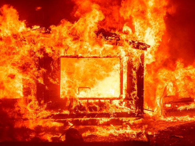 A mobile home and car burn at Spanish Flat Mobile Villa as the LNU Lightning Complex fires tear through unincorporated Napa County, Calif., on Tuesday, Aug. 18, 2020. Fire crews across the region scrambled to contain dozens of wildfires sparked by lightning strikes as a statewide heat wave continues. (AP Photo/Noah Berger)